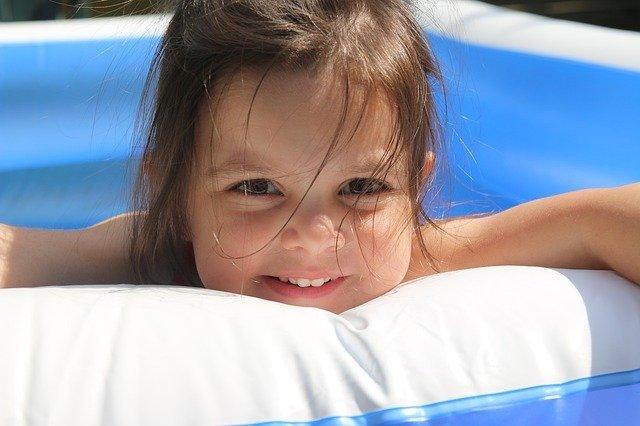 Wasserrutsche für den Garten: Mädchen lächelt aus Planschbecken.