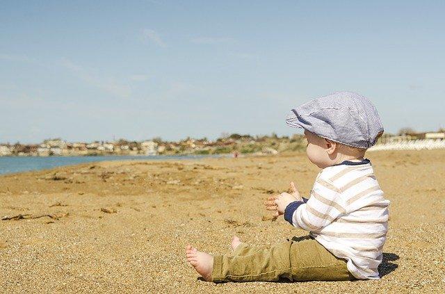 Kind am Strand - Baby wirft Kopf hin und her.