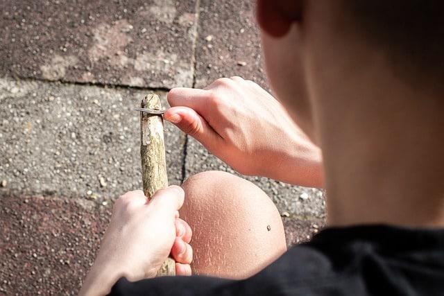 Kind schnitzt mit einem Taschenmesser für Kinder.