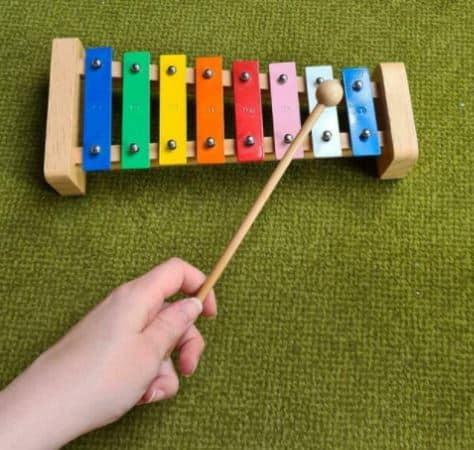 EIn Kind spielt auf einem Xylophon.