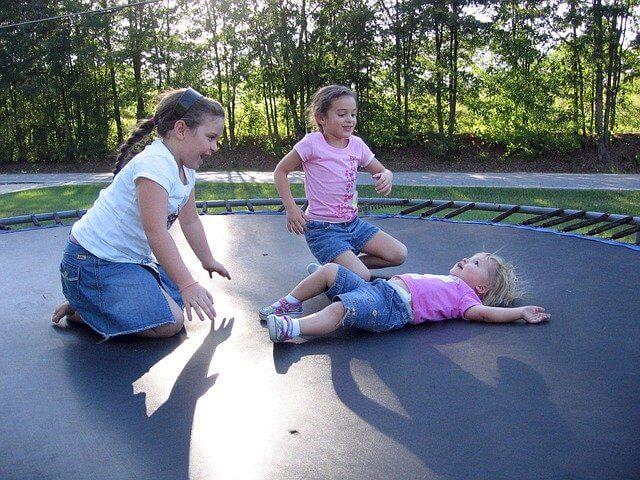 Kinder auf einem Kindertrampolin.